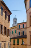 Typical historic Italian town houses with many windows, soft colors and Palazzo Pubblico tower, Siena, Italy Stock Image