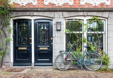 Typical house entrance with two doors and bicycle in Amsterdam. Typical house entrance with two doors, window, and bicycle in the old town of Amsterdam royalty free stock photography