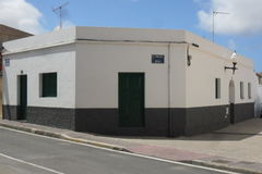 A typical house in the island of Fuerteventura in the Canary Islands. It is a Canarian emblem. The wall and the flat roof are white and the door, the windows royalty free stock photo