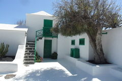 A typical house in the island of Lanzarote in the Canary Islands. It is a Canarian emblem. The walls and the flat roof are white and the door, the windows and royalty free stock image