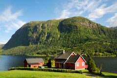 Typical house on the shore of fjord. Detached small house is situated on the shore of blue fjord opposite the sheer green mountain cliff. The smallholding has Royalty Free Stock Photos