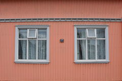 Typical Icelandic house facade in salmon pink color made of corrugated iron and with white wooden windows in Reykjavik Stock Image