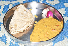 Typical Indian dinner. On a steel plate containing Indian bread called Roti, Indian curry called Dal Fry and two pieces of onions Stock Image