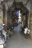 A Typical Indian Narrow Passageway. A typical Indian passageway with bikes, cables and posters. These alleyways are years old Stock Photo