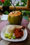 Typical Indonesian Dish: Nasi Ayam Plecing Chicken with rice and special sauce and young coconut vertical full straw.  stock photo