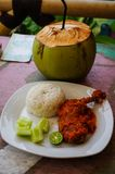 Typical Indonesian Dish: Nasi Ayam Plecing Chicken with rice and special sauce and young coconut vertical.  royalty free stock images