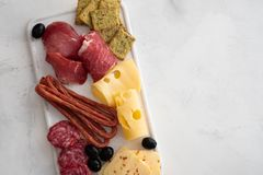Typical italian antipasto,with prosciutto, ham, cheese and olives on white background. Top view with copy space. royalty free stock photo