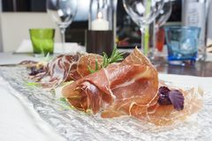 Tray of cold sliced. Typical italian cold sliced wirh Bresaola, ham, salami, rocket with Pine nuts stock photography