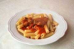 Typical italian dish - pasta with tomato. This is a typical Italian dish. This is a steaming plate of pasta with meat sauce with pork ribs. In Italy pasta is one Royalty Free Stock Images