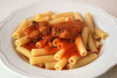 Typical italian dish - pasta with tomato. This is a typical Italian dish. This is a steaming plate of pasta with meat sauce with pork ribs. In Italy pasta is one Stock Photography