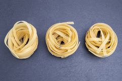 Three nests of Italian pasta online. Typical Italian pasta with spaghetti or yellow noodles in the shape of a nest royalty free stock photography
