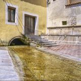 Typical italian square with fountain and laundry Royalty Free Stock Image