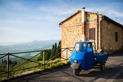 Typical Italian three-wheeler in front of brick house Stock Photography