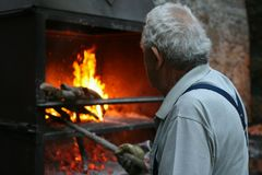 A typical Italian village. Gray-haired old man lights a fire in the oven royalty free stock image
