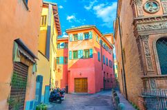 Typical italian yard, traditional buildings with colorful bright walls and bikes on the street in old historical city centre of Bo stock image