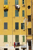 Typical Italy. A view of a yellow house with green shutters in Rome,Italy. Some of the occupiers have their laundry hung out to dry. A typical scene all over stock photo