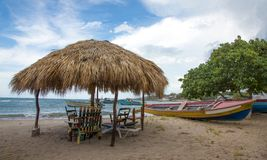 Typical Jamaican beach shelter and fishing boats Stock Photos