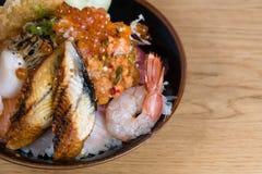 Typical Japanese fish donburi, shrimp tempura, raw shrimps, salmon fillets, grilled tuna, caviar, tuna tartare, sliced cucumbers,. Raw sea bass fillets royalty free stock photo