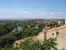 Typical landscape of Languedoc-Roussillon, France. View of the River Orb, with a traditional stone and terracotta building, lush tree growth, distant mountains Royalty Free Stock Images