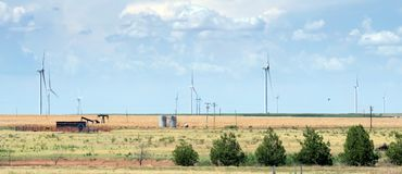 Typical landscape of Texas: endless fields, wind generators, oil. Pumps, rare green bushes. USA royalty free stock photography
