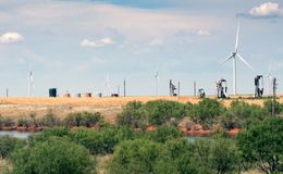 Typical landscape of Texas: endless fields, wind generators, oil. Pumps, rare green bushes. USA royalty free stock photo
