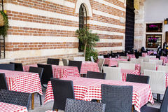 Typical little italian restaurant with empty tables. Typical little italian restaurant with wooden tables and red checkered tablecloths Stock Images