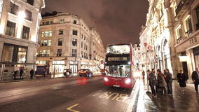 Typical London steet view by night red bus passing by stock footage