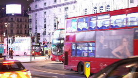 Typical London steet view by night red bus passing by stock video