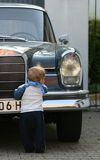 Typical male. Young boy (toddler) standing in front of an oldtimer car Stock Photos