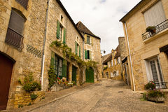 Typical mediaval street Saint-Cyprien Dordogne. Typical mediaval street with stone houses and flowers in the old quarter of Saint-Cyprien Dordogne France Royalty Free Stock Image