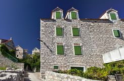 Typical mediterranean house built with stone blocks. Green windows of typical stone built house on mediterranean island of Prvić, Adriatic Sea, Croatia Stock Photos