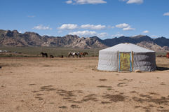 Nomadic yurt in desert. Traditional nomadic yurt or ger in desert with a mountain range in the background Royalty Free Stock Images