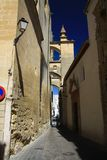 Typical narrow alleyway with arches contrasting with dark blue sky in traditional village Arcos da la Frontera in province stock images