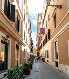 Typical narrow cobbled shopping street of Rome, Italy. With peop Stock Photos