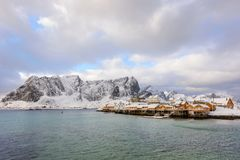Typical Norwegian landscape. Beautiful view of scenic Lofoten Islands winter scenery with traditional yellow fisherman Rorbuer cab. Ins in the historic village stock photos