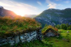 The grass-roofed houses in Norway. Typical norwegian old wooden houses with grass roofs near Sunnylvsfjorden fjord and famous Seven Sisters waterfalls, western Stock Photos