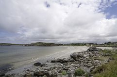 The typical norwegian west coast shoreline with a sandy beach and lot of stones Stock Photos