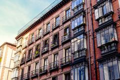 Typical old building facade Madrid, Spain. Brick wall facade and big glass widows royalty free stock image