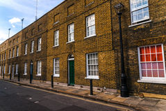 Typical old English buildings, low brick buildings across a narr Stock Photos