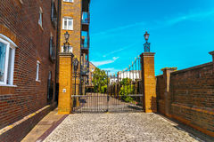 Typical old English buildings, low brick buildings across a narr Stock Photography
