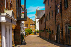 Typical old English buildings, low brick buildings across a narr Stock Photo