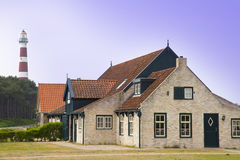 Typical old farmer house on the island Ameland, The Netherlands with famous lighthouse. Royalty Free Stock Images