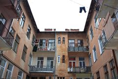 Typical old Lviv patio. Inner view to typical Lviv patio with its open balconies and linen put out to dry outside on clotheslines crossing sky in all directions Royalty Free Stock Photo