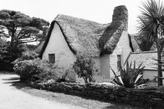 Typical old style thatched roof whitewashed country cottage Stock Photography