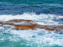 Pacific Ocean waves on Bondi Rocks, Sydney, Australia. Typical pacific Ocean waves and swell crashing or washing over sandstone rocks in sea, North Bondi Beach stock photo