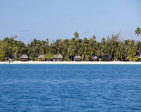 Typical Polynesian landscape - seacoast with palm trees and small houses on water Stock Photography