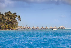 Typical Polynesian landscape - seacoast with palm trees and small houses on water Stock Photo