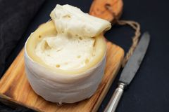 Typical portuguese cheese of serra da estrela. On wooden board on black ceramic background Stock Images