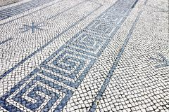 Typical portuguese floor made of small pieces of black and white stone royalty free stock photography