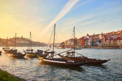 Typical portuguese wooden boats, called  `barcos rabelos `transporting wine barrels on the river Douro with view on Villa Nova de. Gaia  in Porto , Portugal stock images
